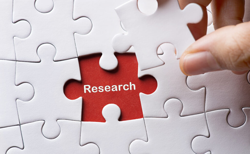 Puzzle with one piece going over the word Research