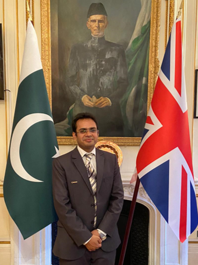 Naveed Hussain standing besides national flags of Pakistan and Britain