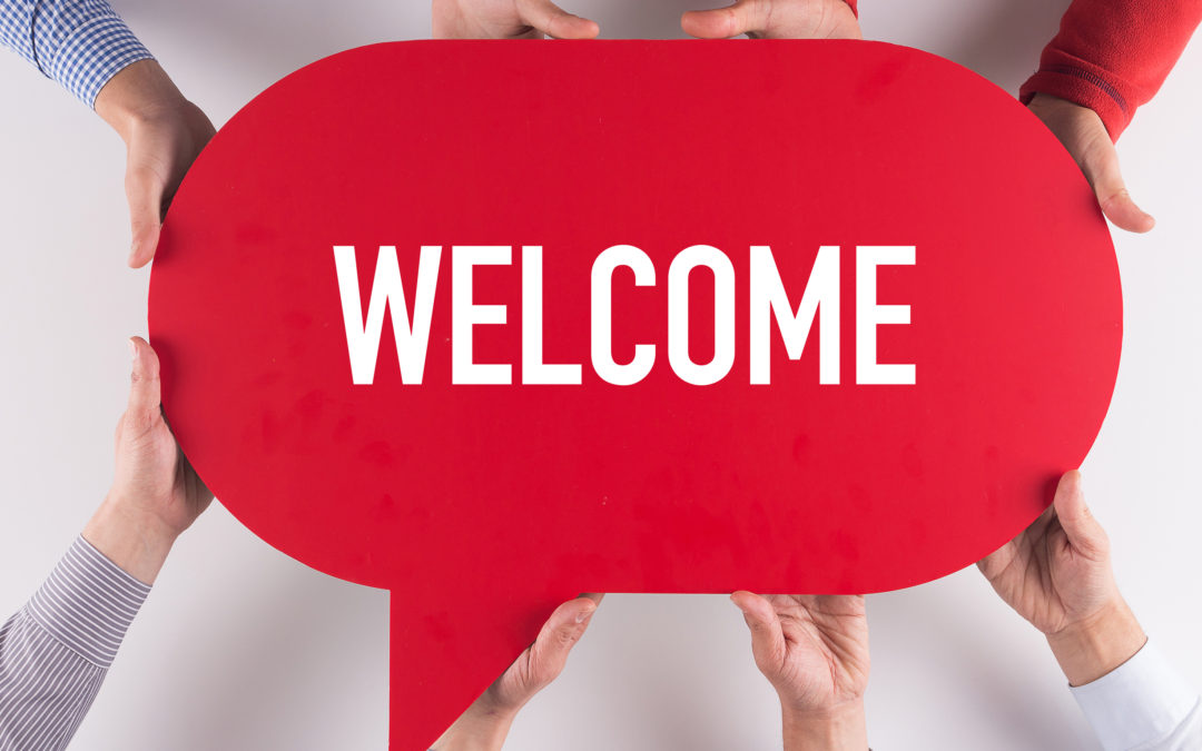 Hands holding red speech bubble reading 'WELCOME'