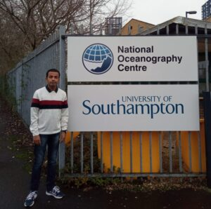 Full length shot of Rajneesh Kumar next to sign reading 'University of Southampton'