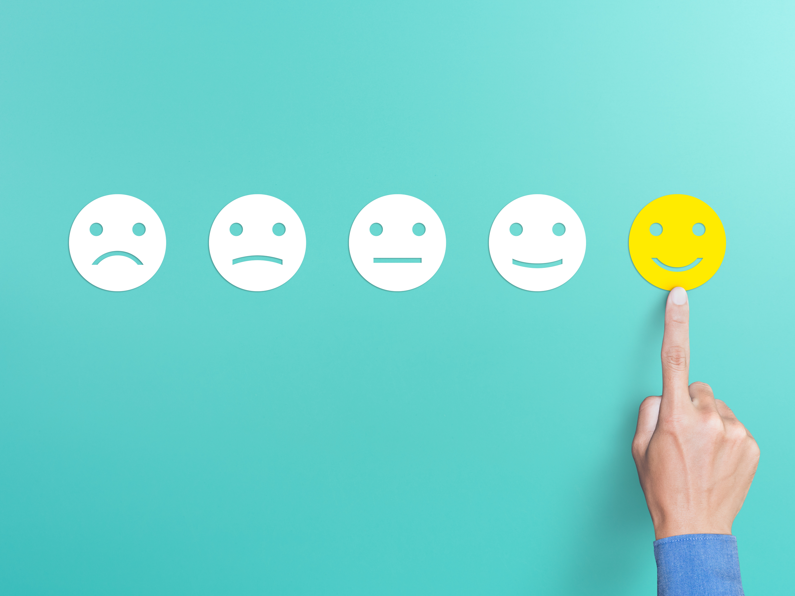 Hand pointing at smiley face icon on rating scale