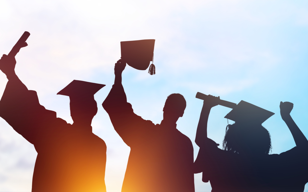 Silhouette of three students in graduation gowns and hats