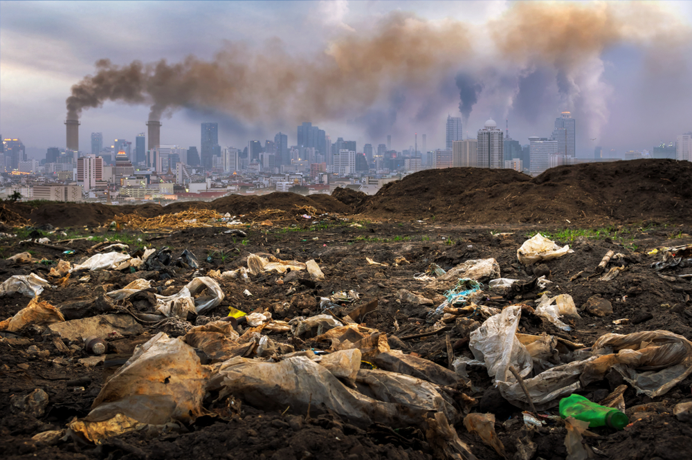 Plastic waste on land with thick, black clouds are coming from a factory nearby